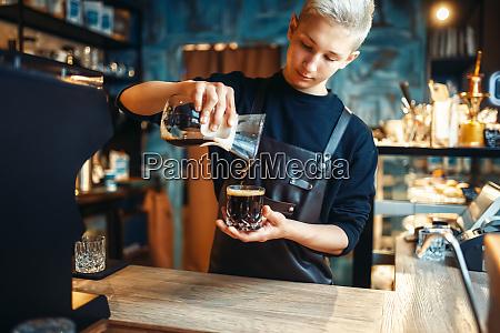 male barista in apron makes fresh