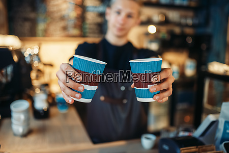 male barista holds two cups of