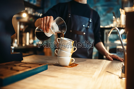 male barista pours black coffee on