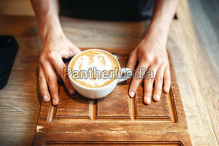 barista holds cup of coffee with