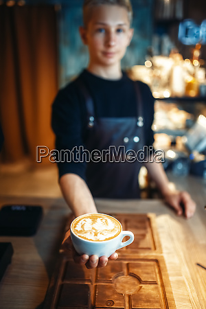 male barista shows cup of coffee