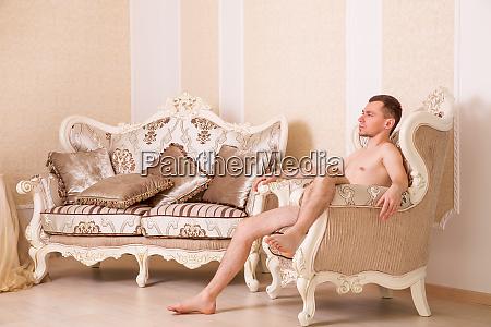 naked macho man sitting on retro