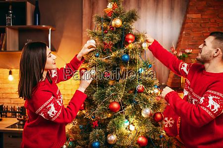 happy love couple decorate christmas tree