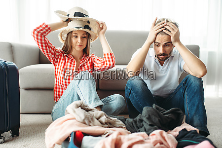 tired couple packing overloaded bag for