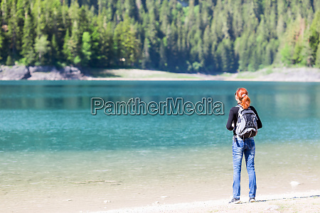 woman with backpack on the lake