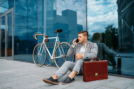 businessman bicyclist in suit talking by