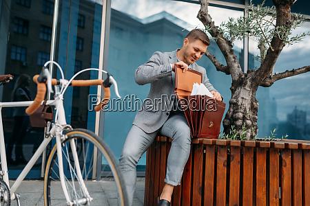 businessman bicyclist puts document into briefcase