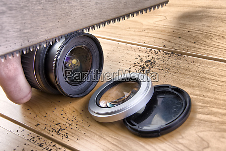 photographer saws a lens