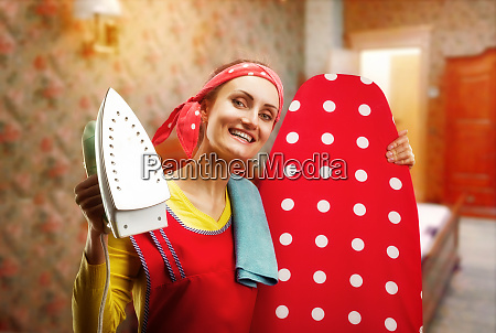 smiling housewife with ironing board and