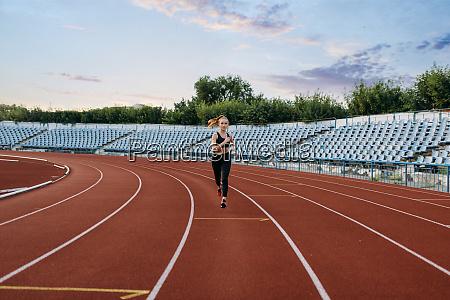 female jogger running training on stadium