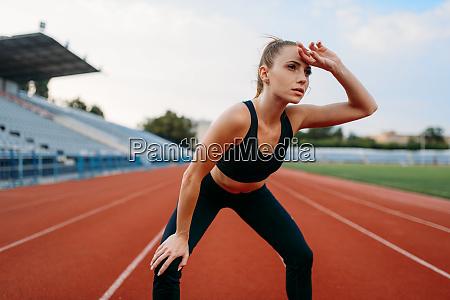 tired female jogger training on stadium