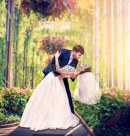 beautiful newlyweds embrace in a green