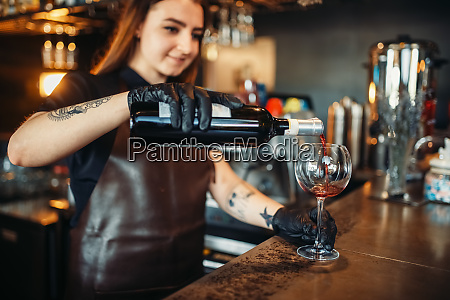 female barman pours red wine into