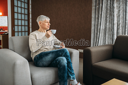 adult man drinks coffee and reading