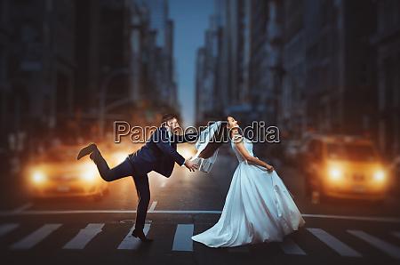 newlyweds crossing a night city street