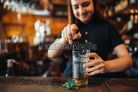female barman mixing at the bar