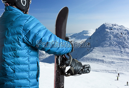 sportsman with snowboard standing in the