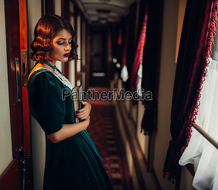 young woman travels vintage train compartment