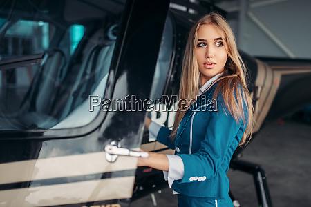 female flight attendant poses against helicopter