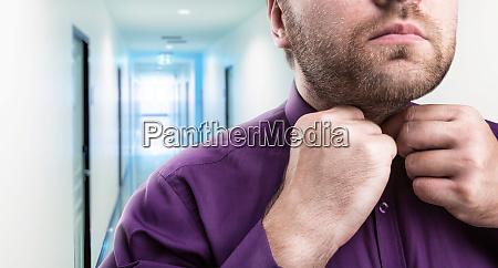bearded man buttons his shirt
