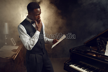 ebony pianist with music notebook on