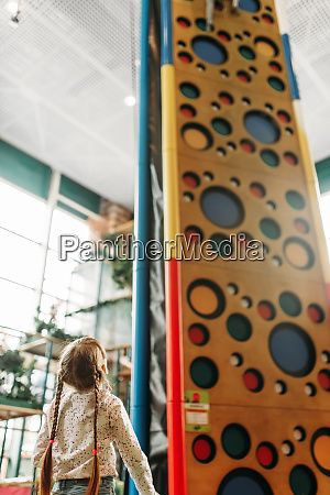 little girl looks on climbing wall