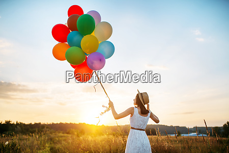 girl with colorful balloons walking in