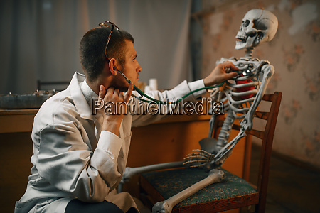 male doctor with stethoscope listening skeleton