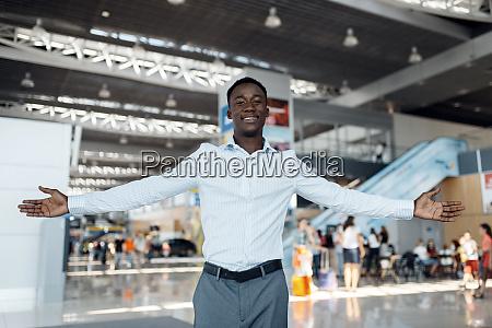 black businessman welcomes guests car showroom