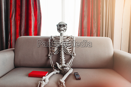 skeleton sitting between book and remote