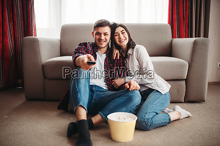 couple sitting on floor and watch