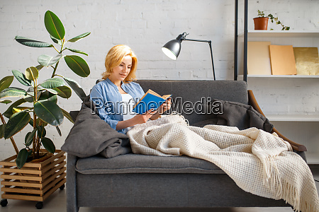young woman under a blanket reading