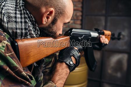 cruel terrorist aiming from a rifle