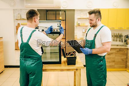 technicians in uniform repair refrigerator at