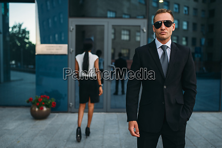 serious bodyguard in suit and sunglasses