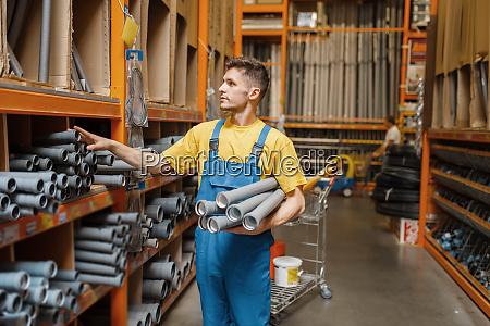 male builder choosing piping in hardware