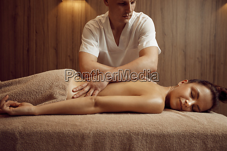 male masseur pampering neck to young