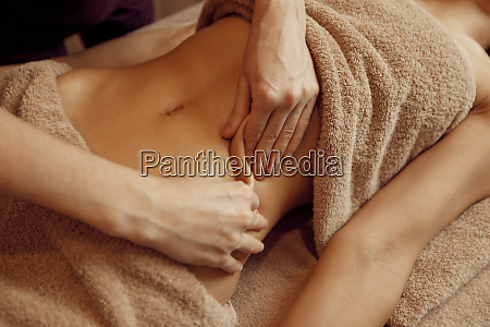 female masseur pampering stomach to young
