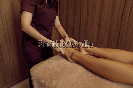 masseur pampering legs to woman closeup