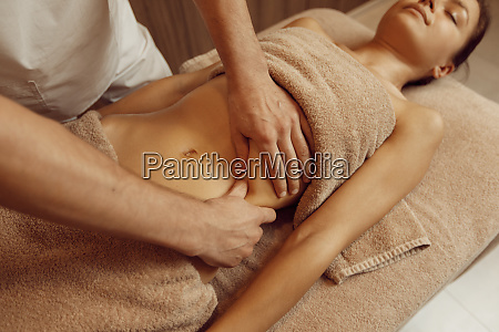 male masseur pampering ribs to young
