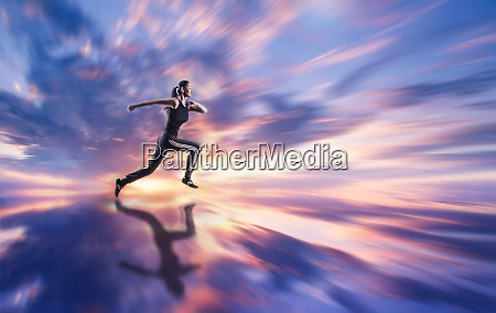woman running against coloured sky