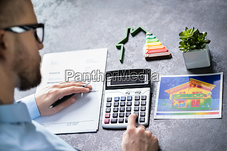 man calculating house energy efficiency rate
