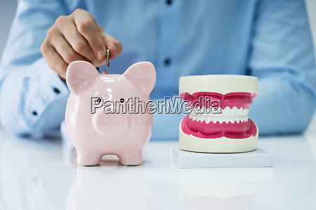 white tooth beside man inserting coin