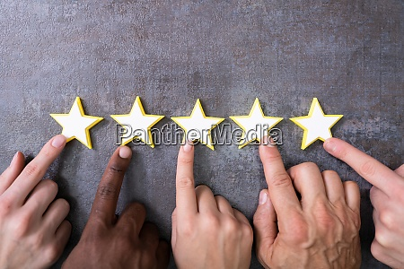 person hands aligning five star rating