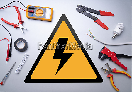 electrician tools around high voltage sign