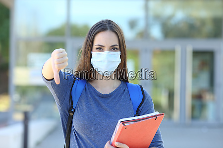 student wearing a mask gesturing thumb