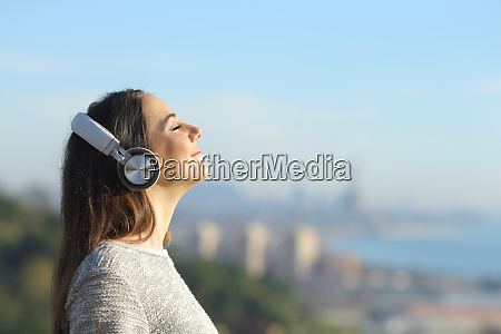 woman listening to music breathing outdoors
