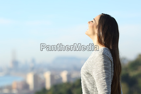 happy woman breathing fresh air with