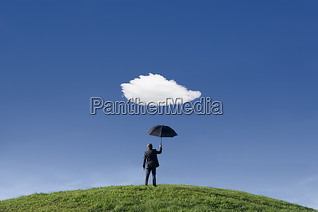 businessman holding umbrella underneath a single
