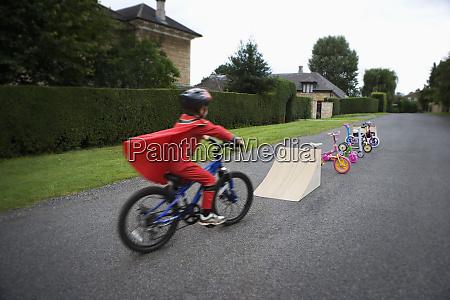 young boy riding bicycle towards ramp